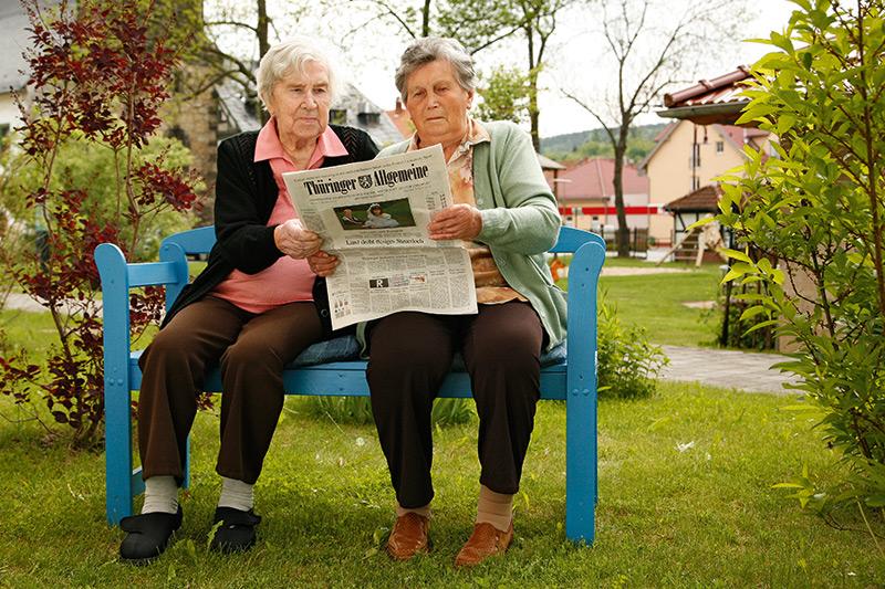 Zwei Omas lesen im Garten Zeitung